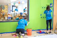A group of volunteers paint a Kindering classroom