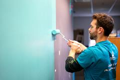 Volunteer paints a Kindering facility