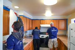 A group of volunteers painting a kitchen in a YouthCare facility