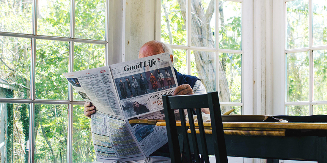 Elderly man reads a newspaper in a sunroom